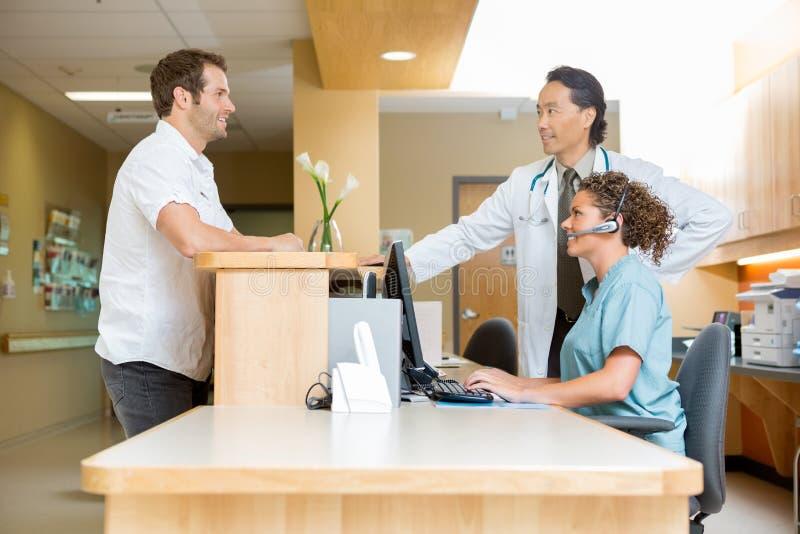Paciente con el mostrador de recepción del doctor And Nurse At imagen de archivo libre de regalías
