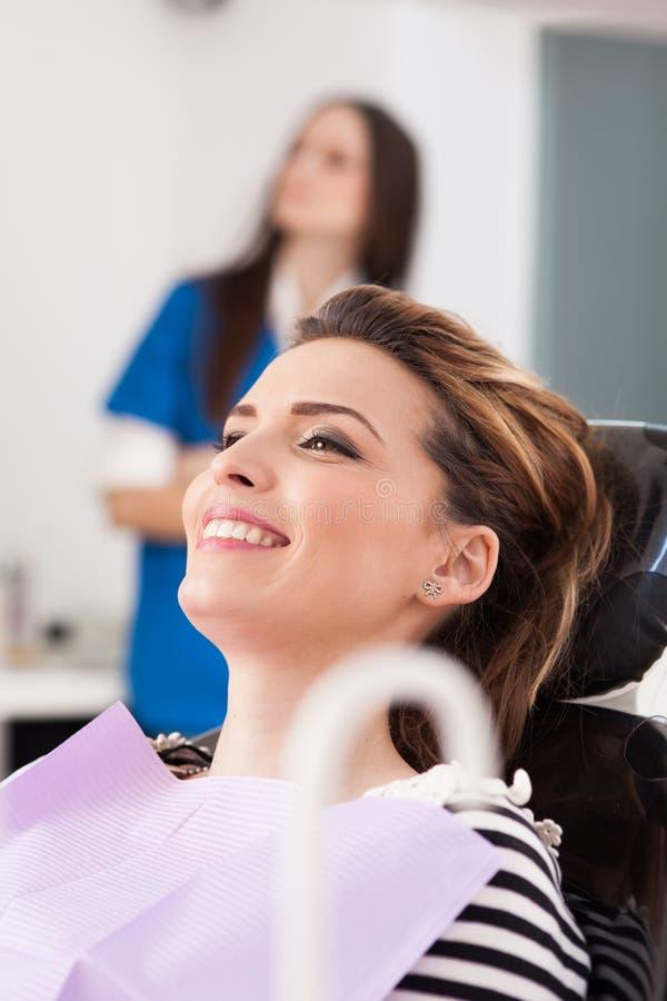 Paciente da mulher no dentista que espera para ser verificado acima imagem de stock