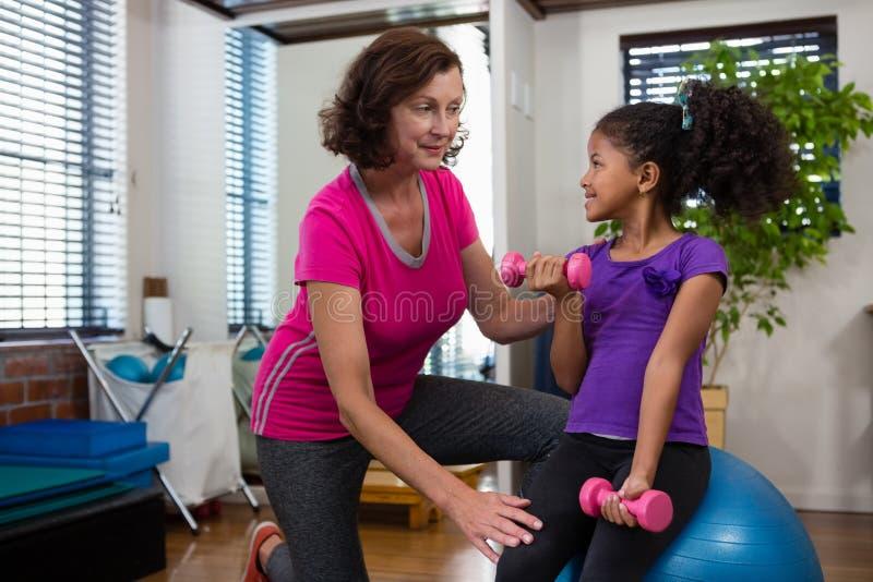 Paciente de ajuda da menina do fisioterapeuta fêmea em executar o exercício com o peso imagens de stock royalty free