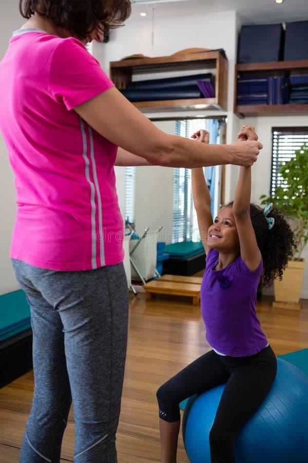 Paciente de ajuda da menina do fisioterapeuta fêmea em executar o exercício com o peso imagens de stock