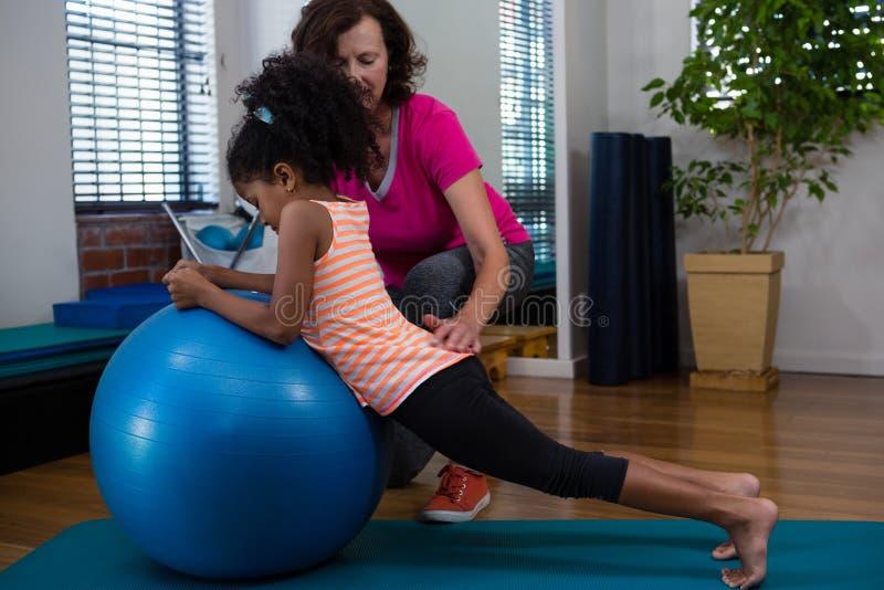 Paciente de ajuda da menina do fisioterapeuta fêmea em executar o exercício de esticão na esteira do exercício fotos de stock royalty free