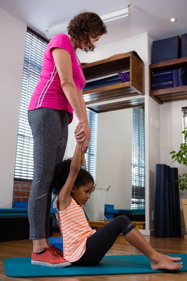 Paciente de ajuda da menina do fisioterapeuta fêmea em executar o exercício de esticão na esteira do exercício fotografia de stock