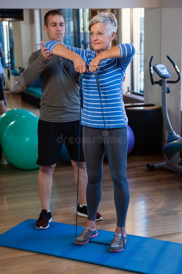 Paciente de ajuda do fisioterapeuta masculino em executar o exercício com a faixa da resistência foto de stock royalty free