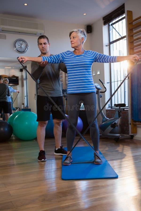 Paciente de ajuda do fisioterapeuta masculino em executar o exercício com a faixa da resistência foto de stock