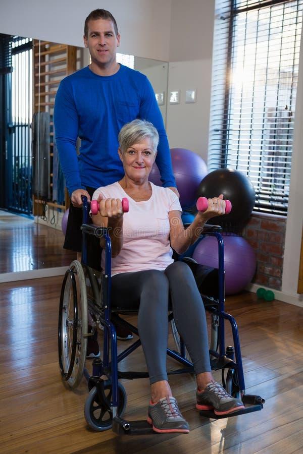 Paciente de ajuda do fisioterapeuta masculino em executar o exercício com o peso fotografia de stock royalty free
