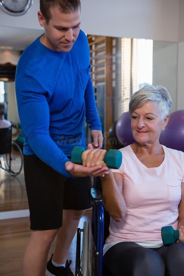 Paciente de ajuda do fisioterapeuta masculino em executar o exercício com o peso foto de stock