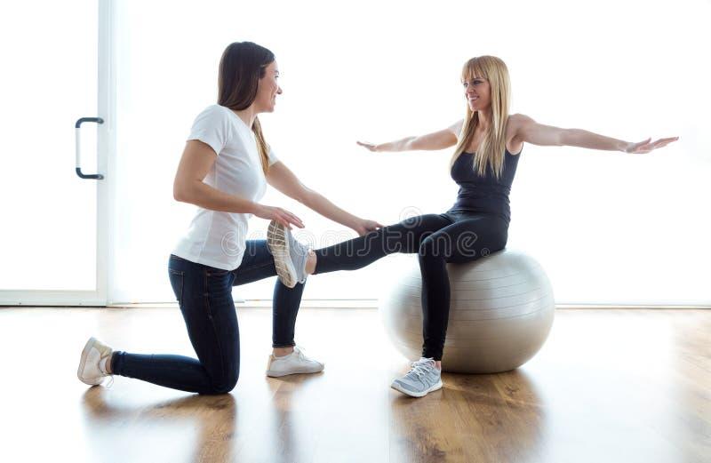 Paciente de ajuda do fisioterapeuta para fazer o exercício na bola da aptidão na físico sala foto de stock