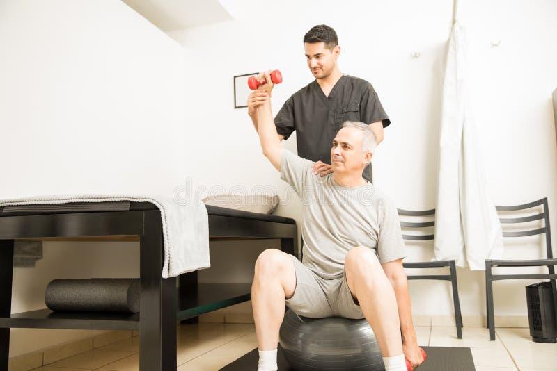 Paciente de ajuda profissional em levantar peso em Physiothera fotografia de stock royalty free