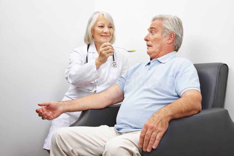 Paciente de alimentación del doctor con las píldoras foto de archivo