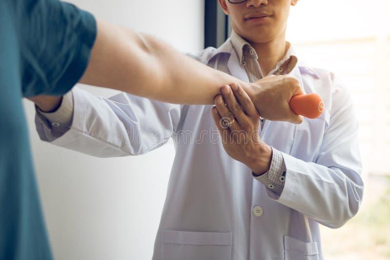 Paciente de ayuda del fisioterapeuta de sexo masculino joven asi?tico con ejercicios de elevaci?n de las pesas de gimnasia en ofi fotos de archivo libres de regalías