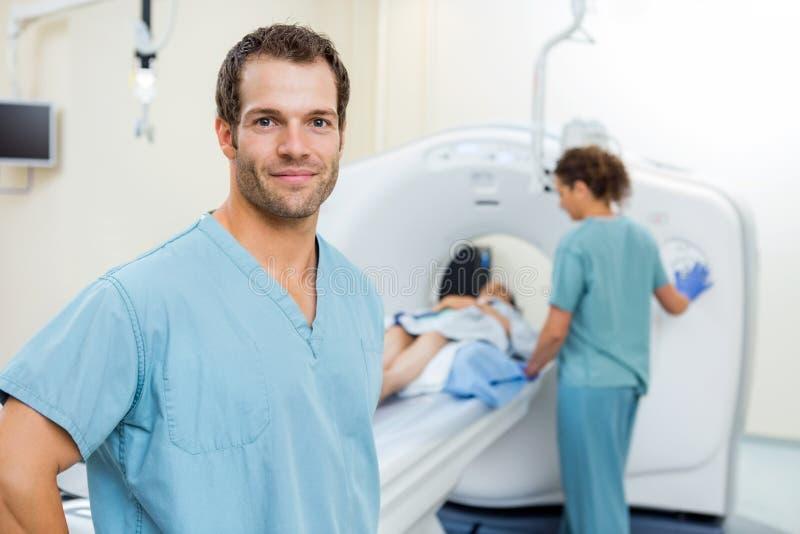 Paciente de With Colleague Preparing de la enfermera para la exploración del CT fotografía de archivo