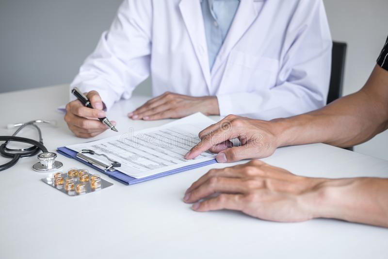 Paciente de consulta do doutor que discute algo sintoma da doença e para recomendar métodos de tratamento, apresentando resultado imagem de stock