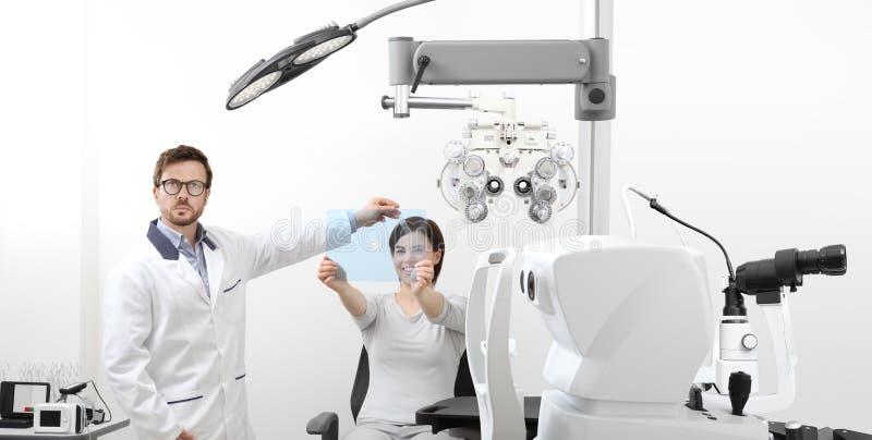 Paciente de exame da mulher da visão do optometrista que aponta no HOL fotos de stock