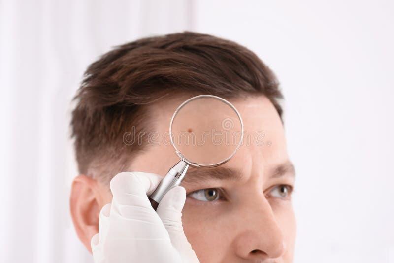 Paciente de examen del dermatólogo con la lupa en clínica fotografía de archivo