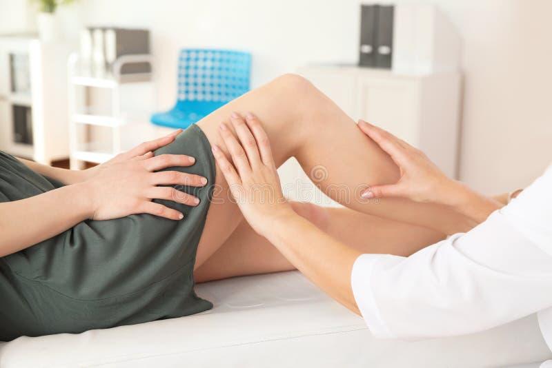 Paciente de examen del doctor con problemas de la rodilla en clínica fotografía de archivo libre de regalías