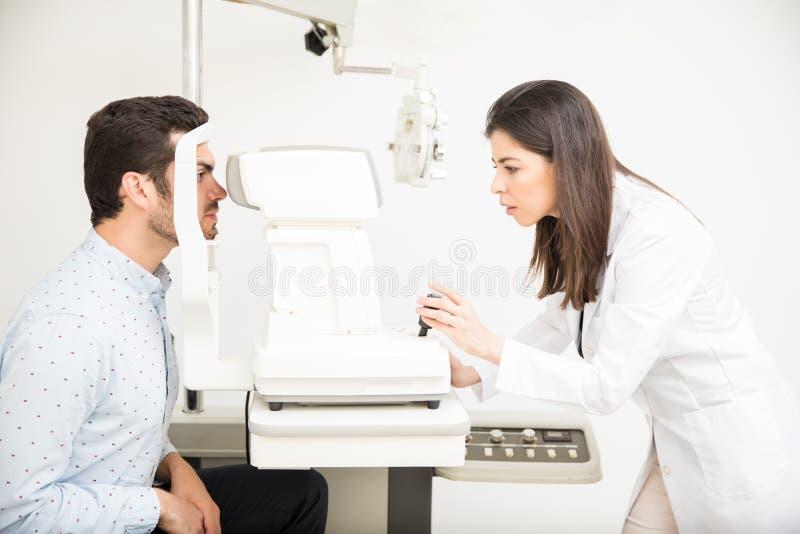 Paciente de examen del oftalmólogo joven en clínica foto de archivo libre de regalías