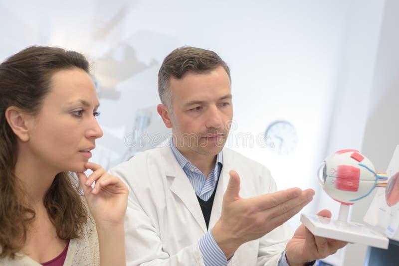 Paciente de explicação do oftalmologista com olho modelo fotos de stock