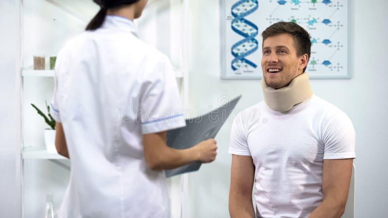 Paciente de información del doctor en cuello cervical de la espuma sobre el buen resultado de la radiografía, rehabilitación foto de archivo libre de regalías