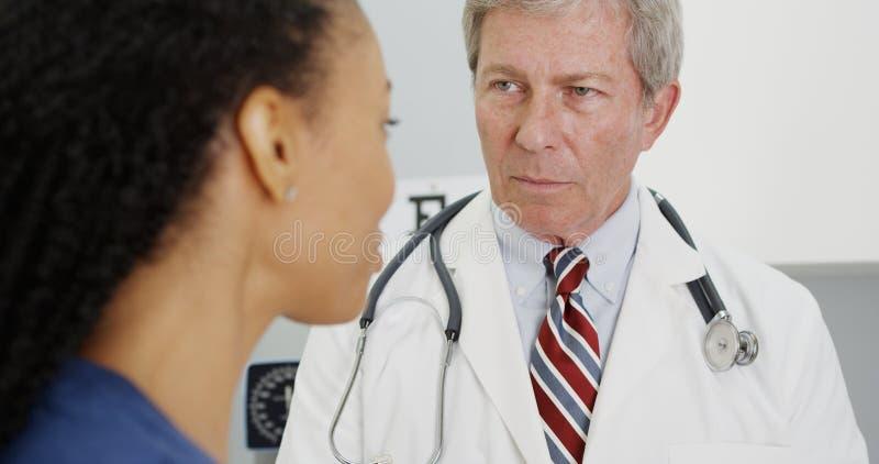 Paciente de la mujer negra que habla con su doctor foto de archivo