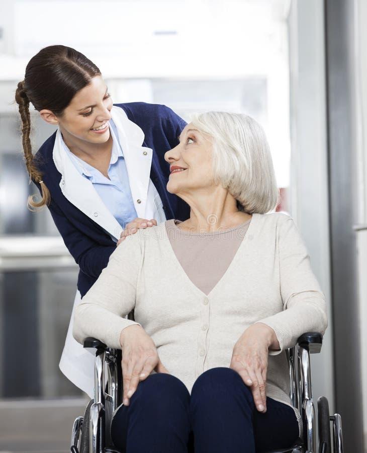 Paciente de Looking At Senior do fisioterapeuta que senta-se na cadeira de rodas fotos de stock royalty free