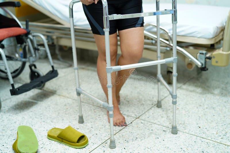 Paciente de meia idade asiático da mulher da senhora que cai e para andar com o caminhante na sala de visitas fotos de stock royalty free