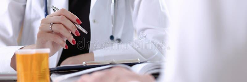 Paciente de relleno del doctor de la mano del control de la pluma femenina de la plata imagenes de archivo