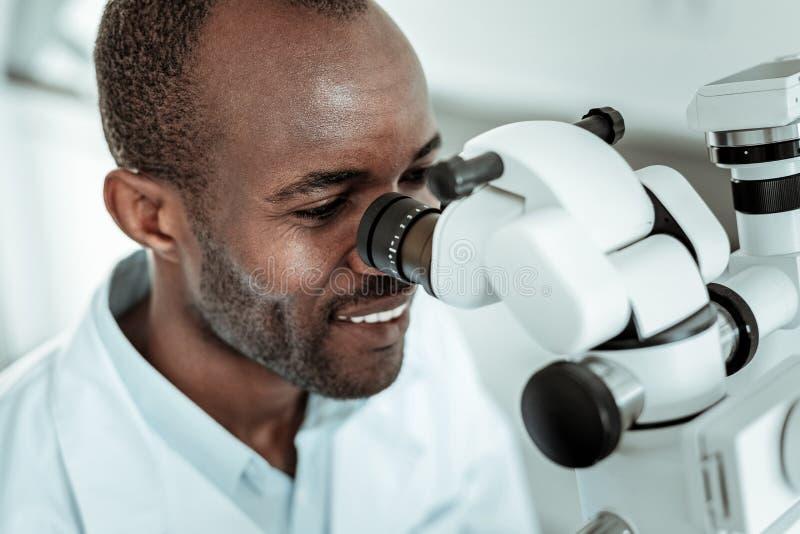 Paciente de repaso del doctor positivo profesional con el microscopio especial imagenes de archivo