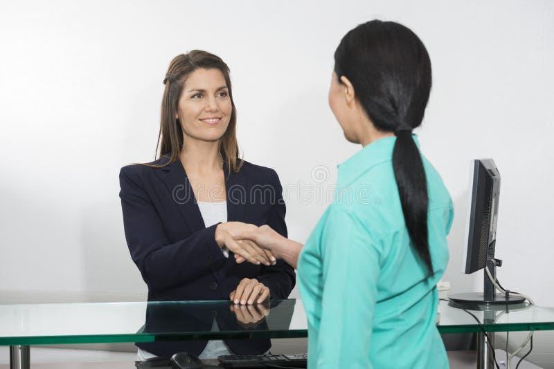 Paciente de Shaking Hand With do recepcionista no hospital imagens de stock