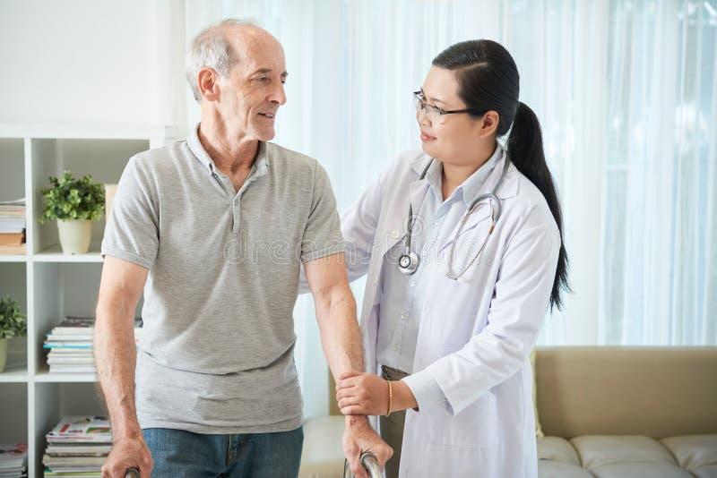 Paciente de visita da enfermeira foto de stock