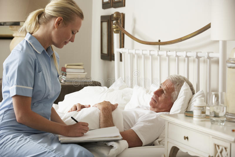Paciente de Visiting Senior Male de la enfermera en cama en casa imagen de archivo