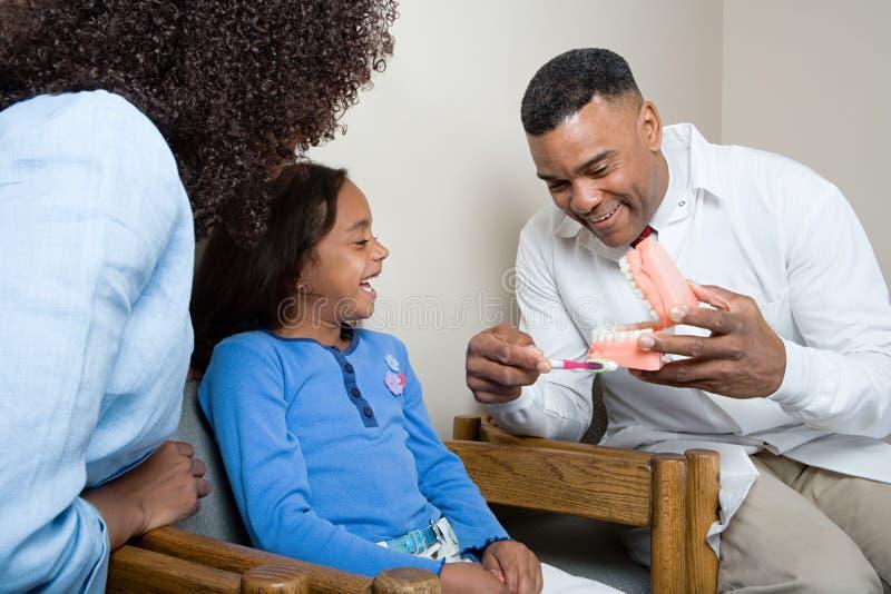 A paciente del dentista mostrando cómo limpiar los dientes imagen de archivo
