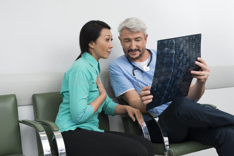 Paciente del doctor Explaining X-ray To Surprised fotografía de archivo libre de regalías