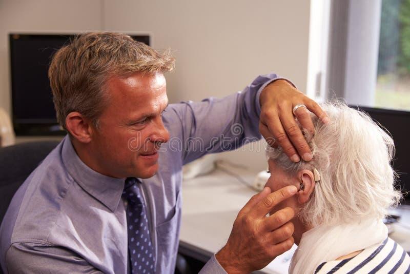 Paciente del doctor Fitting Senior Female con el audífono imagenes de archivo