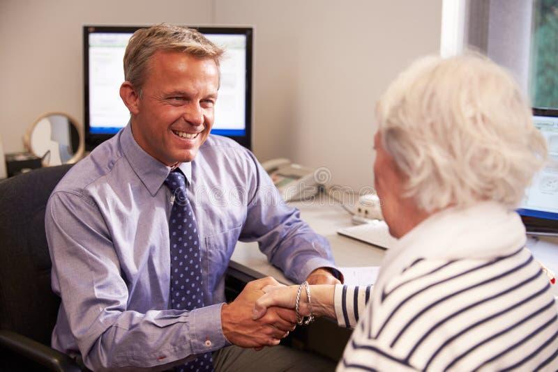 Paciente del doctor Greeting Senior Female con el apretón de manos foto de archivo
