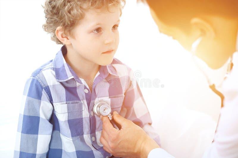 Paciente del doctor y del niño El médico examina al niño pequeño por el estetoscopio Concepto de la terapia del ` s de la medicin foto de archivo