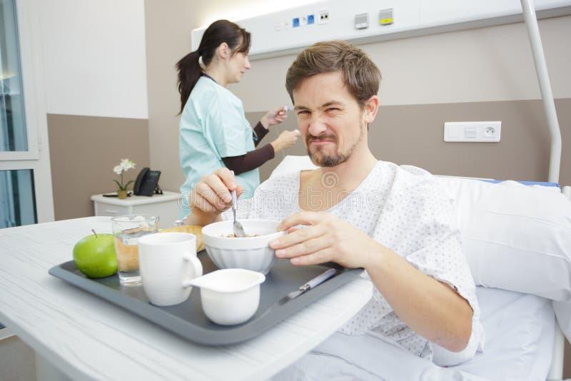 Paciente disgustado desayunando en el hospital imagen de archivo