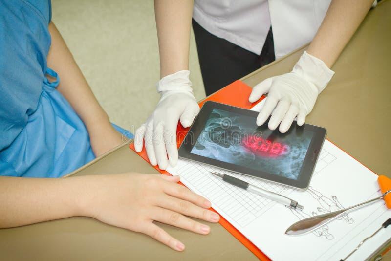 Paciente do doutor Discussing Records With que usa o PC da tabuleta de Digitas fotos de stock