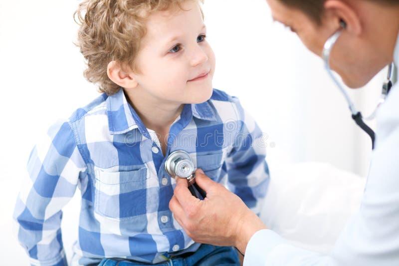 Paciente do doutor e da criança O médico examina o rapaz pequeno pelo estetoscópio Conceito da terapia do ` s da medicina e das c fotografia de stock