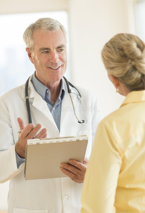 Paciente do doutor Explaining Report To na clínica fotografia de stock royalty free