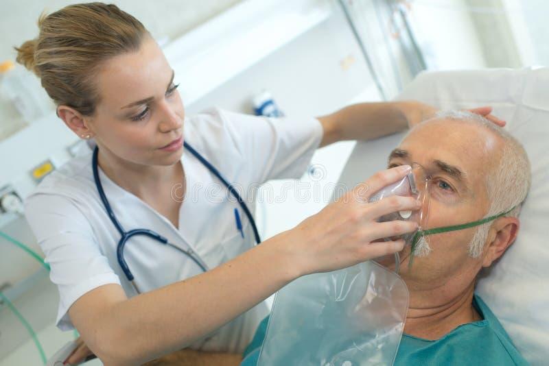 Paciente do homem adulto no hospital com máscara de oxigênio fotos de stock royalty free