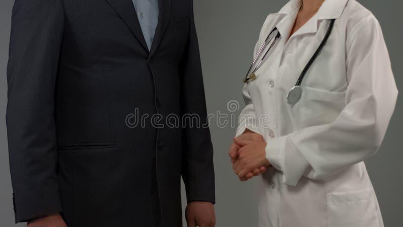 Paciente do homem de negócios que fala com o doutor fêmea, discutindo o diagnóstico, cuidados médicos imagem de stock