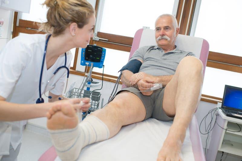 Paciente do pé de envolvimento do doutor no hospital foto de stock