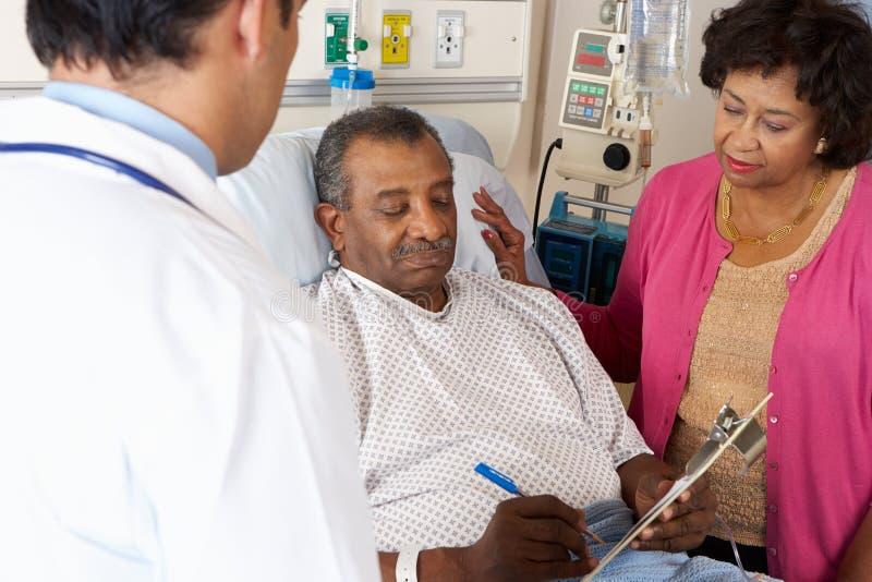 Paciente do sénior do doutor Explaining Consentimento Formulário  imagens de stock