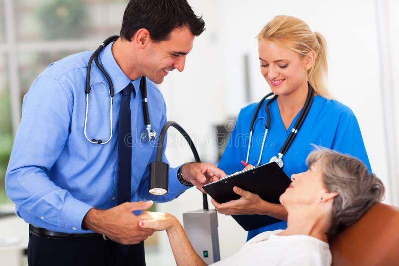 Paciente do sênior do dermatologista imagem de stock royalty free
