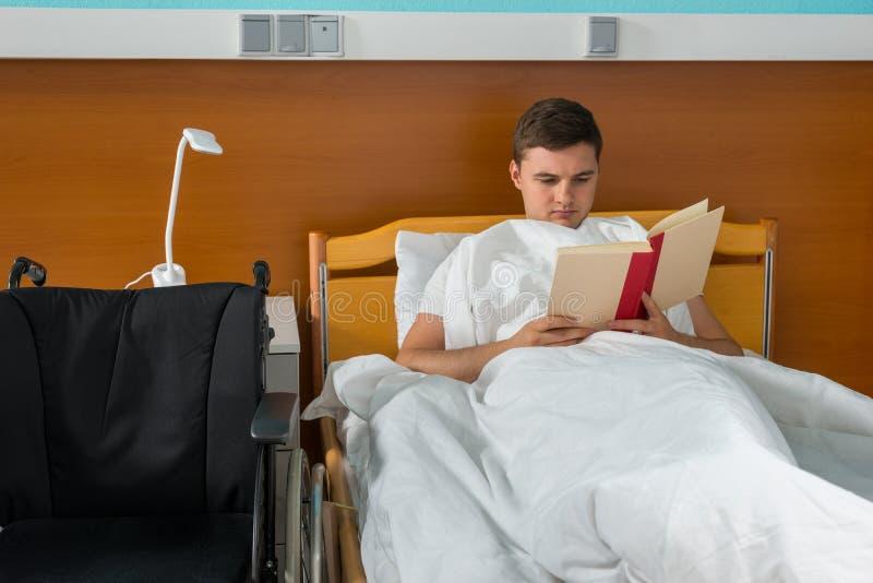 Paciente doente masculino novo que encontra-se na cama de hospital e que lê um b imagem de stock
