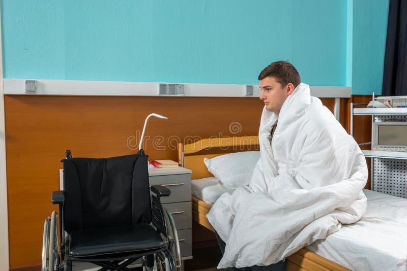Paciente doente masculino que senta-se na cama de hospital coberta com a edredão imagens de stock