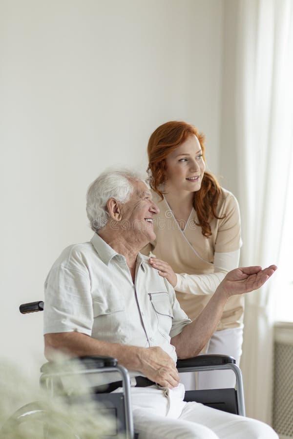 Paciente em uma cadeira de rodas que sorri ao falar a uma enfermeira em uma casa da idade avançada imagens de stock