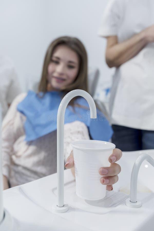 Paciente en la oficina del dentista que toma una taza de agua después del tratamiento fotos de archivo libres de regalías