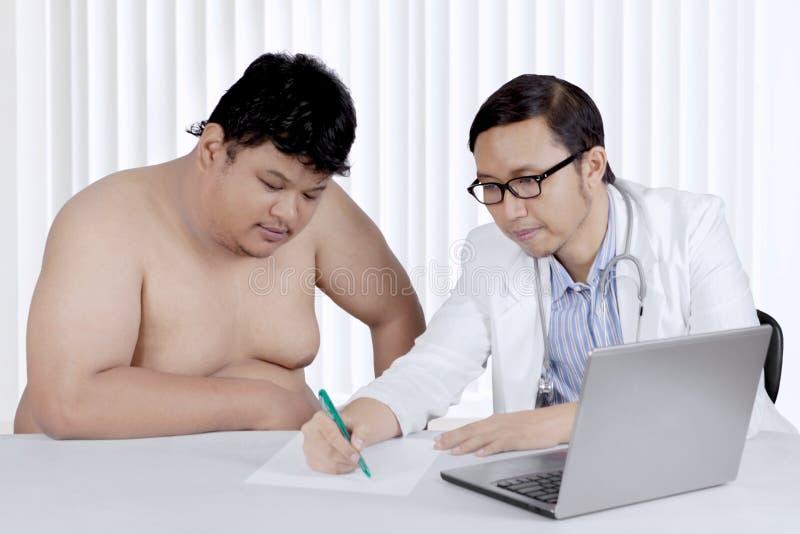 Paciente excesso de peso asiático com um doutor imagens de stock
