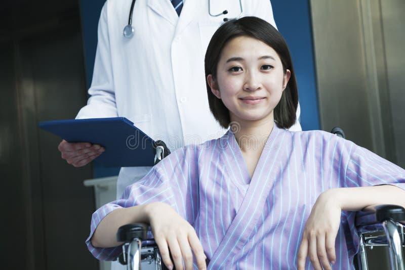 Paciente fêmea de sorriso que senta-se em uma cadeira de rodas, doutor dos jovens que está atrás dela, olhando a câmera imagens de stock